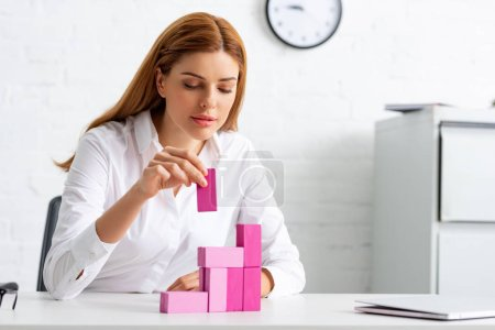 Attractive businesswoman playing pink building blocks at table