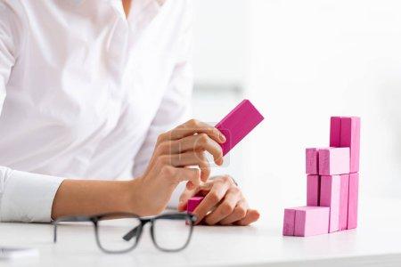 Photo pour Concentration sélective de femme d'affaires empilant pyramide de marketing de blocs roses jeu de bois sur la table - image libre de droit
