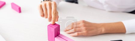 Photo for Cropped view of businesswoman stacking pink building blocks on table, panoramic shot - Royalty Free Image