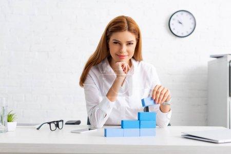 Photo pour Femme d'affaires réussie souriant à la caméra tout en empilant pyramide de marketing de blocs de construction sur la table - image libre de droit