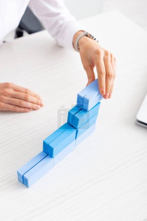 Cropped view of businesswoman stacking blue building blocks near laptop on table