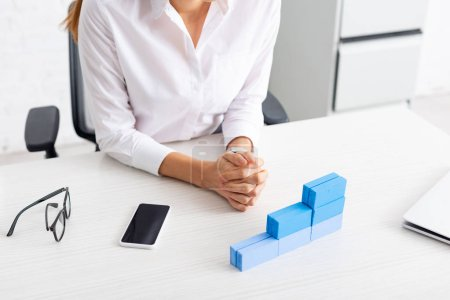 Photo for Cropped view of businesswoman sitting at table with stacked blue building blocks and gadgets - Royalty Free Image