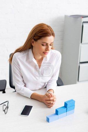 Photo pour Belle femme d'affaires regardant empilés blocs de construction bleus sur la table de travail - image libre de droit