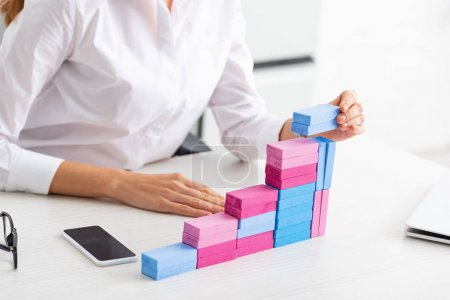 Photo for Cropped view of businesswoman stacking marketing pyramid from building blocks on table - Royalty Free Image