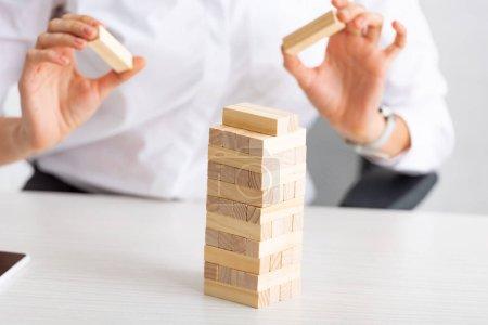 Photo pour Vue recadrée de femme d'affaires empilant des blocs de construction en bois sur la table sur fond gris - image libre de droit