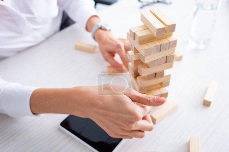 Photo pour Vue recadrée de la femme d'affaires jouant blocs tour en bois jeu près du smartphone à la table - image libre de droit
