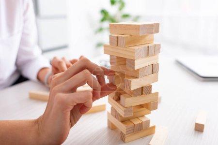 Photo pour Clopped vue de femme d'affaires jouant blocs jeu de bois à la table - image libre de droit
