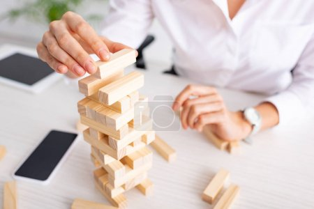 Photo for Selective focus of businesswoman playing blocks wood tower game at table - Royalty Free Image