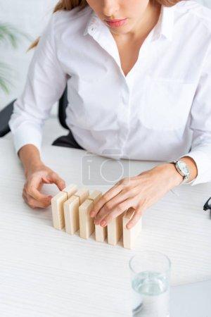 Photo pour Vue recadrée de femme d'affaires empilant des blocs de construction en bois sur la table - image libre de droit