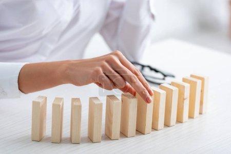 Photo pour Vue recadrée de femme d'affaires jouant des blocs de construction en bois à table - image libre de droit