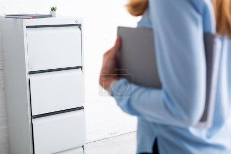 Photo pour Concentration sélective du conducteur de cabinet et de la femme d'affaires tenant le dossier en papier dans le bureau - image libre de droit
