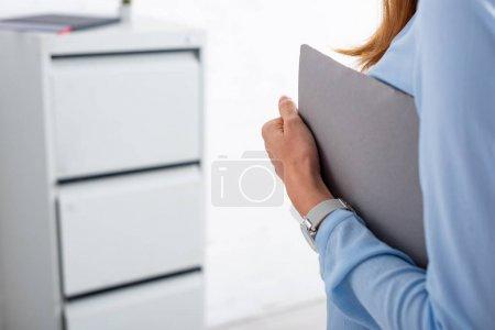 Ausgeschnittene Ansicht einer Geschäftsfrau mit Papiermappe im Büro