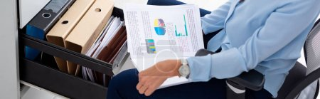 Photo pour Vue agrandie d'une femme d'affaires tenant des papiers avec des graphiques près d'un chauffeur de cabinet ouvert avec des chemises en papier, photo panoramique - image libre de droit
