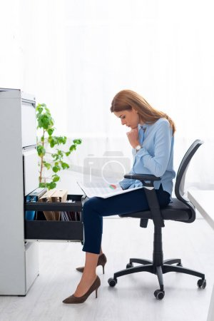 Photo for Side view of businesswoman holding papers with graph while sitting near open cabinet driver - Royalty Free Image