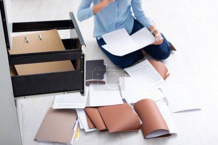 Photo pour Vue recadrée de femme d'affaires avec contrat et documents près du conducteur de l'armoire ouverte sur le sol - image libre de droit