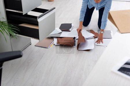 Photo pour Vue croustillante d'une femme d'affaires cherchant un dossier près d'un contrat au bureau - image libre de droit