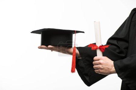 Photo pour Vue croustillante d'un étudiant qui détient un plafond et un diplôme isolés sur blanc - image libre de droit