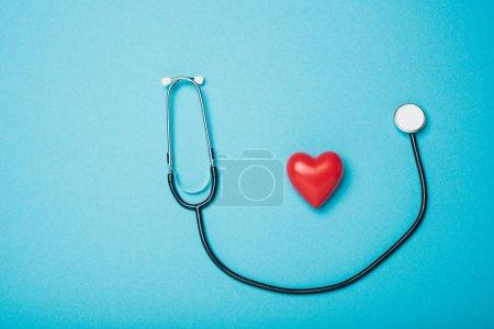 Photo pour Vue de haut du cœur rouge décoratif et du stéthoscope sur fond bleu, concept de la Journée mondiale de la santé - image libre de droit