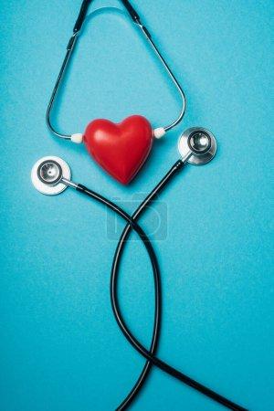 Photo pour Vue de haut du cœur rouge décoratif avec stéthoscope noir sur fond bleu, concept de la Journée mondiale de la santé - image libre de droit