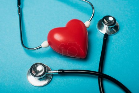 Photo for Decorative red heart and black stethoscope on blue background, world health day concept - Royalty Free Image