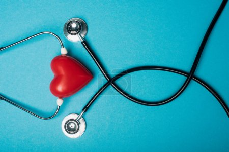 Photo for Top view of decorative red heart and black stethoscope on blue background, world health day concept - Royalty Free Image