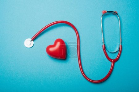 Photo for Top view of decorative heart next to red stethoscope on blue background, world health day concept - Royalty Free Image