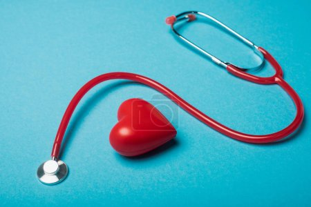 Decorative heart next to red stethoscope on blue background, world health day concept