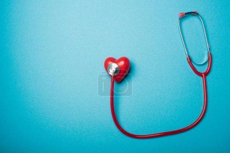 Photo pour Vue du dessus du coeur décoratif relié au stéthoscope rouge sur fond bleu, concept de journée mondiale de la santé - image libre de droit