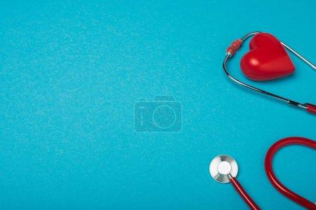 Photo pour Coeur décoratif et stéthoscope sur fond bleu, concept de la Journée mondiale de la santé - image libre de droit
