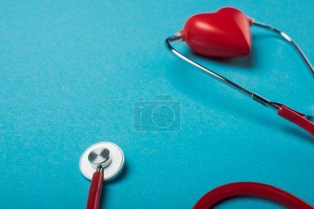 Photo pour Stéthoscope relié au coeur rouge décoratif sur fond bleu, concept de journée mondiale de la santé - image libre de droit
