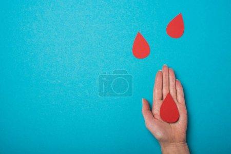Photo pour Vue en haut de la paume de la femme avec gouttes de sang décoratives sur fond bleu, concept de la Journée mondiale de la santé - image libre de droit
