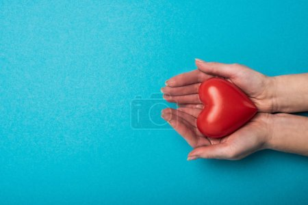 Top view of woman holding decorative heart on blue background, world health day concept