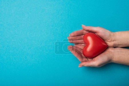 Photo pour Vue du dessus de la femme tenant coeur décoratif sur fond bleu, concept de journée mondiale de la santé - image libre de droit
