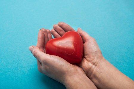 Photo pour Vue agrandie d'un cœur rouge décoratif entre les mains d'une femme sur fond bleu, concept de la Journée mondiale de la santé - image libre de droit