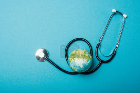 Photo for Top view of globe and stethoscope on blue background, world health day concept - Royalty Free Image