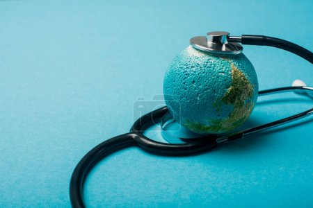 Photo for Stethoscope connected with globe on blue background, world health day concept - Royalty Free Image