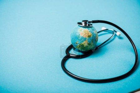 Photo pour Stethoscope avec globe sur fond bleu, concept de la Journée mondiale de la santé - image libre de droit