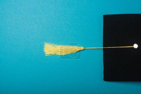 Photo pour Vue du dessus du bonnet de graduation noir avec pompon jaune sur fond bleu - image libre de droit