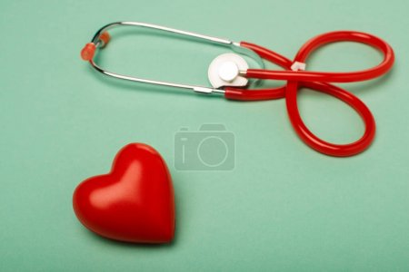 Estetoscopio con corazón rojo decorativo sobre fondo verde, concepto del día mundial de la salud