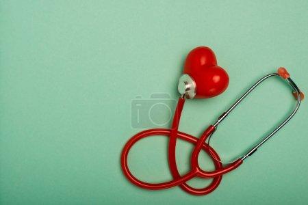 Photo pour Vue de haut du stéthoscope rouge relié au coeur décoratif sur fond vert, concept de la Journée mondiale de la santé - image libre de droit