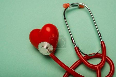 Photo pour Stéthoscope rouge relié au coeur décoratif sur fond vert, concept de la Journée mondiale de la santé - image libre de droit