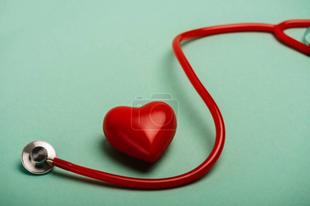 Decorative heart next to red stethoscope on green background, world health day concept
