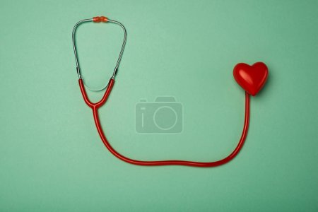 Photo pour Vue du stéthoscope et du cœur rouge décoratif sur fond vert, concept de la Journée mondiale de la santé - image libre de droit