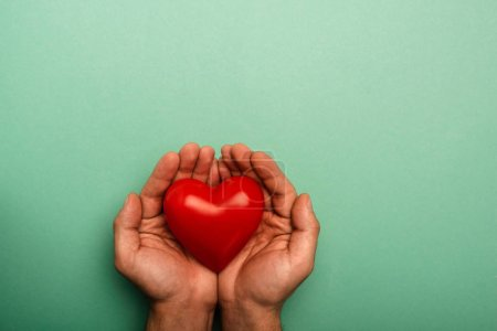 Photo pour Top view of decorative red heart in man hands on green background, World Health Day concept - image libre de droit