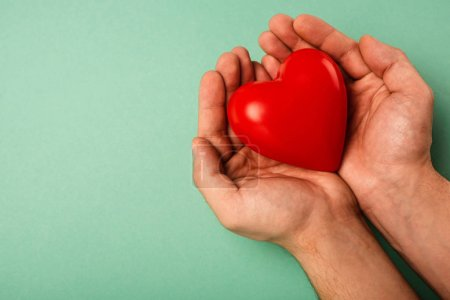 Cropped view of decorative red heart in man hands on green background, world health day concept