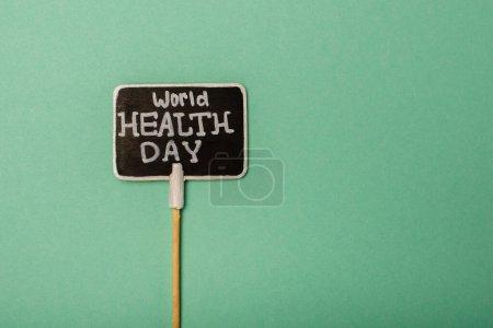 Photo pour Vue du dessus de la carte avec lettrage Journée mondiale de la santé sur fond vert - image libre de droit