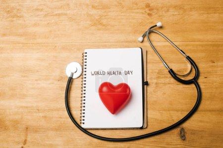 Photo pour Vue en haut du stéthoscope, coeur décoratif sur cahier avec lettrage de la Journée mondiale de la santé sur fond en bois - image libre de droit