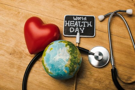 Top view of decorative red heart, stethoscope, globe and card with world health day lettering on wooden background