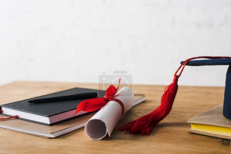Photo for Notebooks with pen, diploma and graduation cap on table on white background - Royalty Free Image