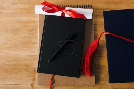 Photo pour Vue en haut des cahiers, du stylo, du diplôme et du panache rouge sur fond de bois - image libre de droit